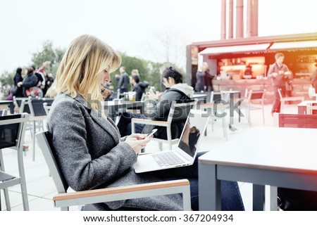 Portrait of a young beautiful businesswoman who is holding portable laptop computer while sitting in a coffee shop outdoors and chatting on smart-phone. Flare light - stock photo