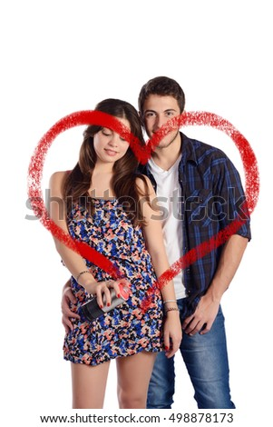 Portrait of a young beautiful couple drawing a heart with aerosol can. Isolated white background.