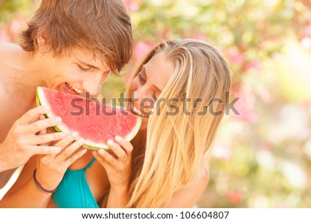 Portrait of a young beautiful couple eating watermelon