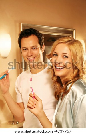 portrait of a young beautiful couple in thair bath cleaning their teeth