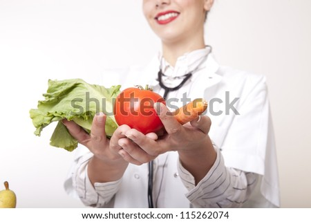 Portrait of a young beautiful female doctor holding fresh vegetables. - stock photo