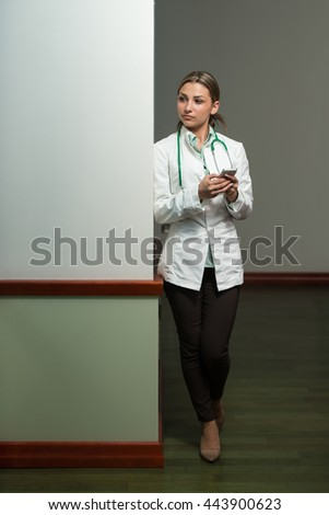 Portrait Of A Young Beautiful Female Doctor Writing Text On Mobile - Healthcare Worker Working Online