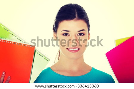 Portrait of a young beautiful female student holding workbooks. - stock photo