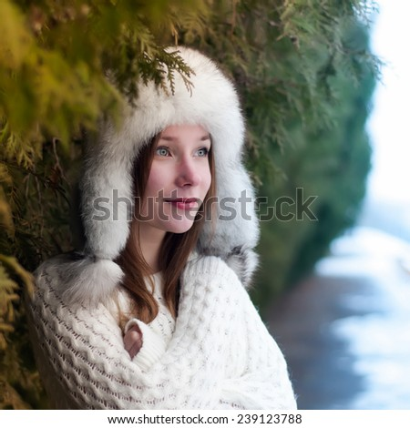 Portrait of a young beautiful girl in a cap with earflaps in a cool winter park