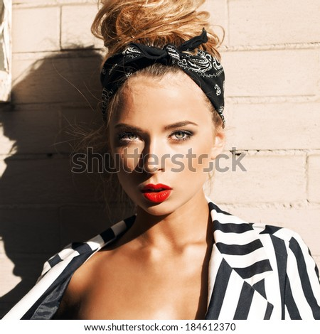 portrait of a young beautiful girl in stylish white striped jacket looking into the camera poses against white brick wall - stock photo