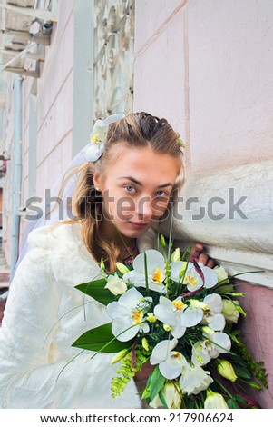 Portrait of a young beautiful girl in the dress of the bride before the wedding with a bouquet of flowers