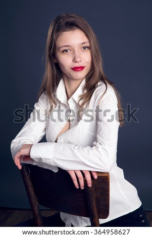Portrait of a young beautiful girl on a dark blue background. Woman in a white shirt sitting on a stool and looking to the side.