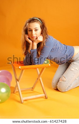 portrait of a young beautiful girl on orange background with balloons