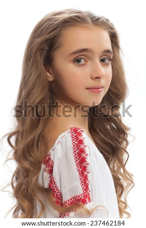portrait of a young beautiful girl with a wreath of flowers on her head in a white dress with red embroidery isolated on white background - stock photo