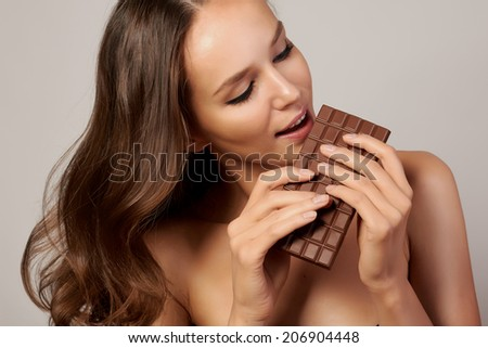 Portrait of a young beautiful girl with dark curly hair, bare shoulders and neck, holding a chocolate bar to enjoy the taste and are dieting, healthy eating and organic foods - stock photo