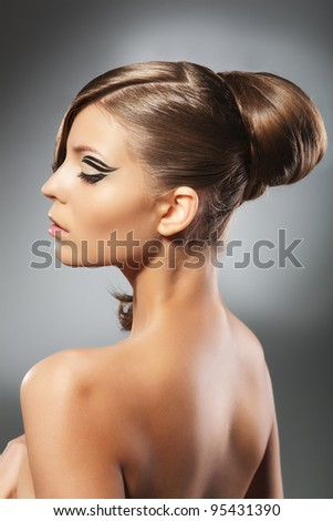 Portrait of a young beautiful girl with hairstyle turned back to the camera on a grey background - stock photo