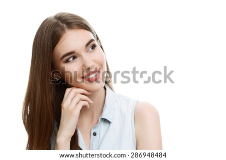 Portrait of a young beautiful girl with long brown hair wearing blue denim blouse, smiling and holding her hand near face looking to the left tilting her head, isolated on white background - stock photo