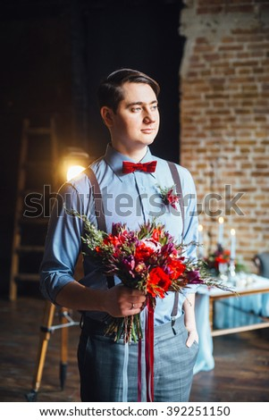 Portrait of a young beautiful groom in the interior.