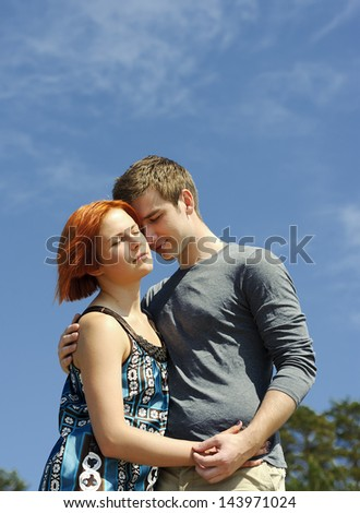 Portrait of a young beautiful happy couple outside hugging and smiling