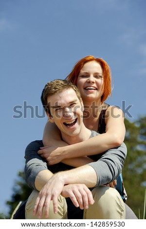 Portrait of a young beautiful happy couple outside man carrying woman smiling