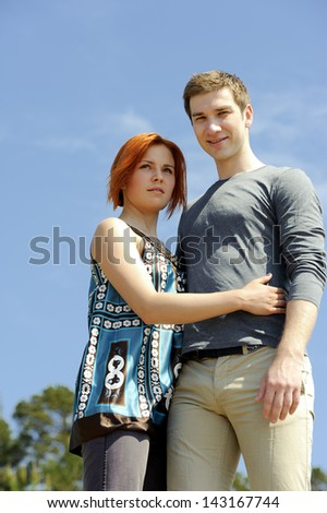 Portrait of a young beautiful happy couple outside standing hugging and smiling