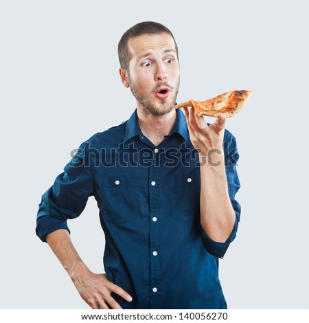 portrait of a young beautiful man eating a slice of pizza margherita - stock photo