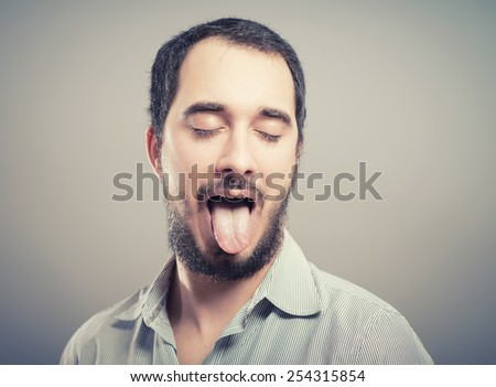 portrait of a young beautiful man showing tongue, face expression - stock photo