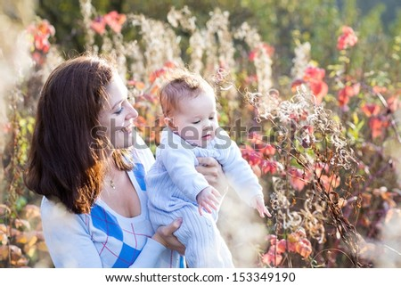 Portrait of a young beautiful mother and her new born baby in a sunny autumn park - stock photo