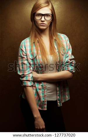 Portrait of a young beautiful red-haired wearing trendy glasses and casual clothes and posing over golden background. Studio shot. - stock photo