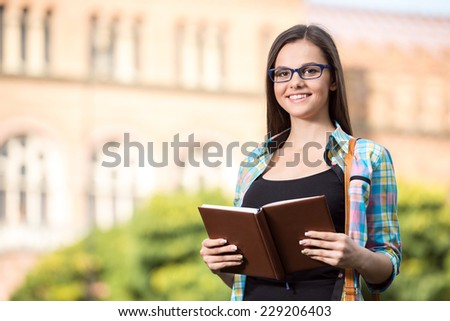 Portrait of a young beautiful student with university building in the background.