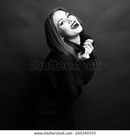 Portrait of a young beautiful stylish woman against black background