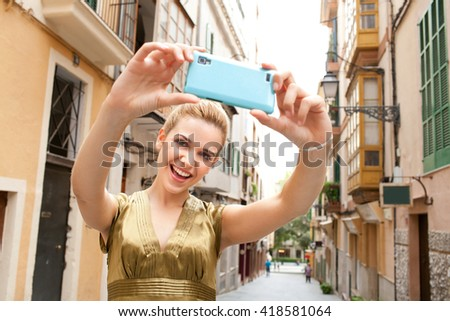 Portrait of a young beautiful tourist woman holding up a smart phone, taking selfies photos with fun expressions in a destination city street on holiday. Woman using technology, travel lifestyle. - stock photo
