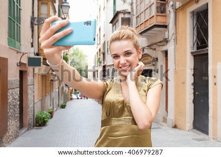 Portrait of a young beautiful tourist woman holding up smart phone device to take selfies in city street on holiday, smiling and posing outdoors. Girl using enjoying technology networking, exterior.