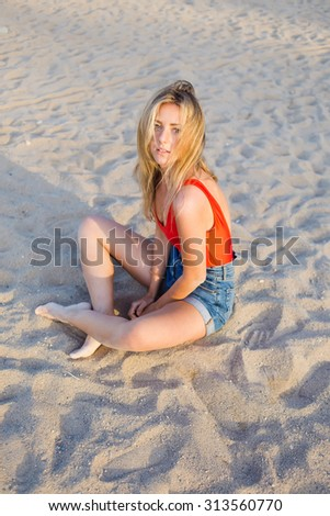 Portrait of a young beautiful woman dressed in stylish clothes sitting on the beach and enjoying leisure time after strolling by coastline, attractive female posing for the camera sitting on the sand - stock photo
