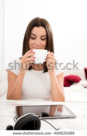 Portrait of a young beautiful woman drinking coffee, and using a tablet pc