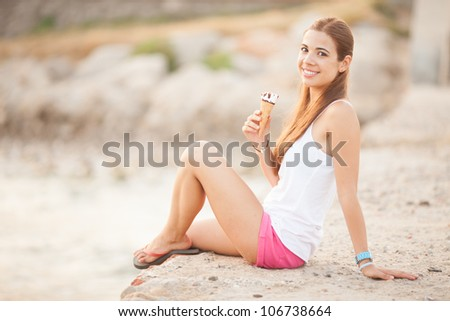portrait of a young beautiful woman eating ice-cream cone - stock photo