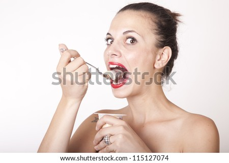 Portrait of a young beautiful woman eating pudding.