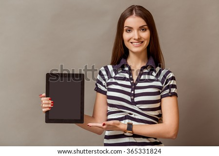 Portrait of a young beautiful woman in a striped shirt, showing a blank black screen tablet computer, smiling, looking at camera, on a gray background - stock photo