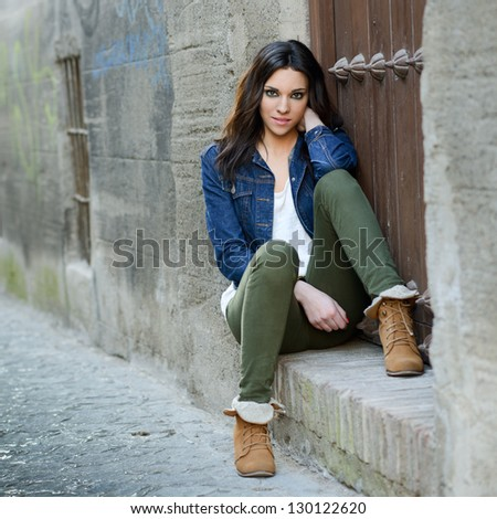 Portrait of a young beautiful woman in a urban background - stock photo