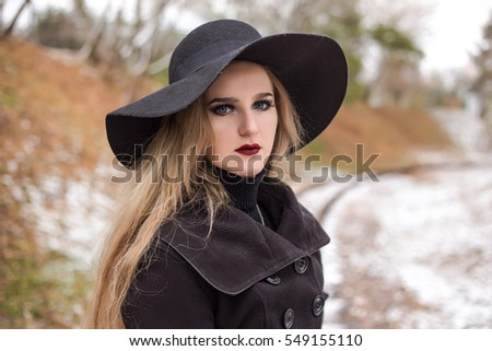 Portrait of a young beautiful woman in black hat retro style.