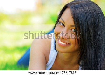 Portrait of a young beautiful woman lying on the grass and smiling