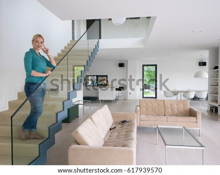 portrait of a young beautiful woman on the stairs in her luxurious home