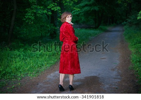Portrait of a young beautiful woman posing outdoors in a red velvet coat.
