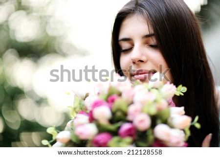 Portrait of a young beautiful woman smelling flowers - stock photo