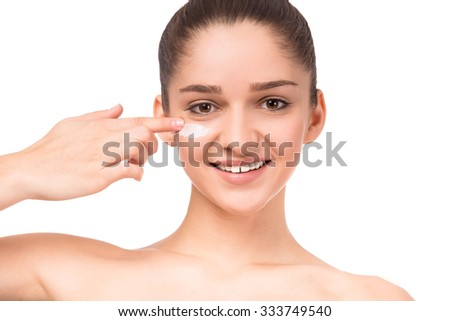 Portrait of a young beautiful woman using cream, isolated on a white background - stock photo