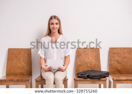 Portrait of a young, beautiful woman waiting job interview, sitting in the hallway, on gray background. Studio shoot - stock photo