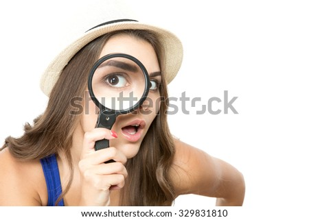 Portrait of a young beautiful woman wearing a hat posing, holding a reading-glass so her eye is very big and funny, isolated on white background