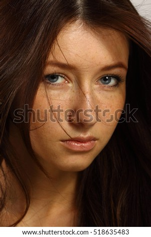 Portrait of a young, beautiful woman with freckles close-up