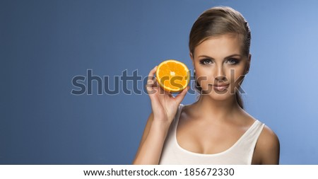 Portrait of a young beautiful woman with orange  - stock photo