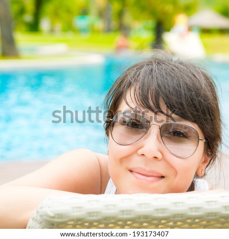 Portrait of a young beautiful woman with sunglasses lying on a sun lounger on against of the pool background