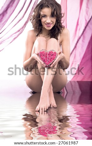 Portrait of a young beauty holding a heart of roses - stock photo