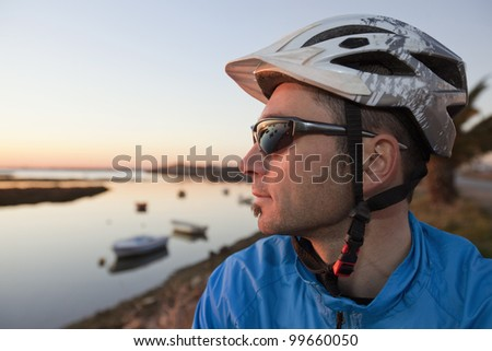 Portrait of a young bicyclist in helmet and glasses with sunset at the background
