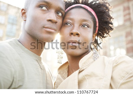 Portrait of a young black couple of tourists visiting the city at sunset, holding their heads together.
