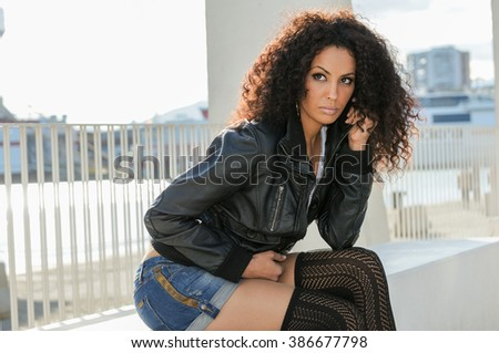 Portrait of a young black woman, afro hairstyle, in urban background. Girl wearing denim jeans shorts and leather jacket.