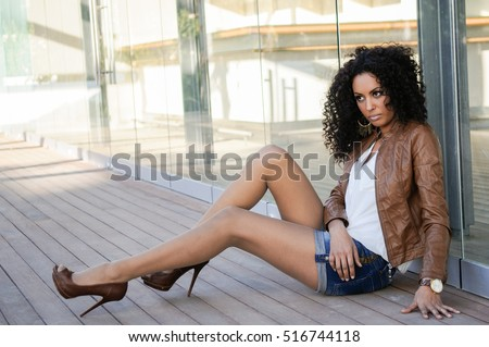Portrait of a young black woman, afro hairstyle, wearing beige leather jacket, in urban background